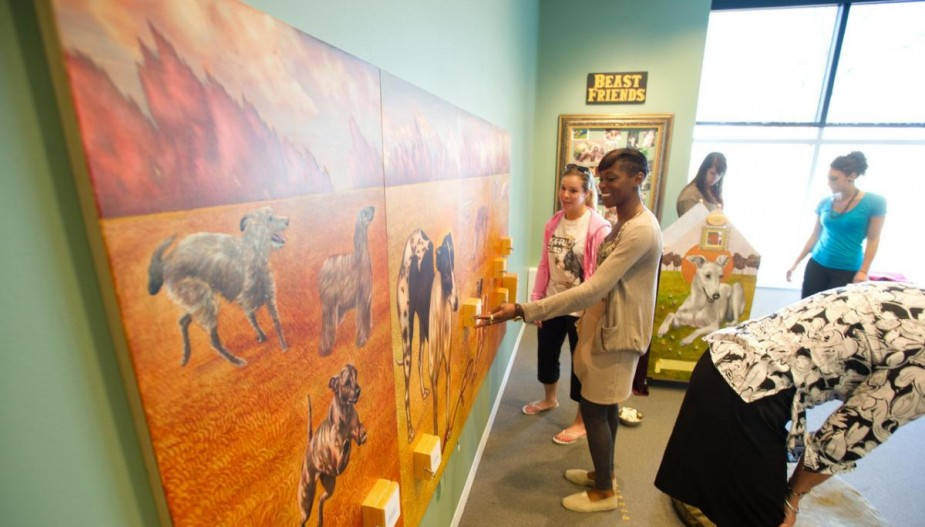 Students examine artwork in gallery
