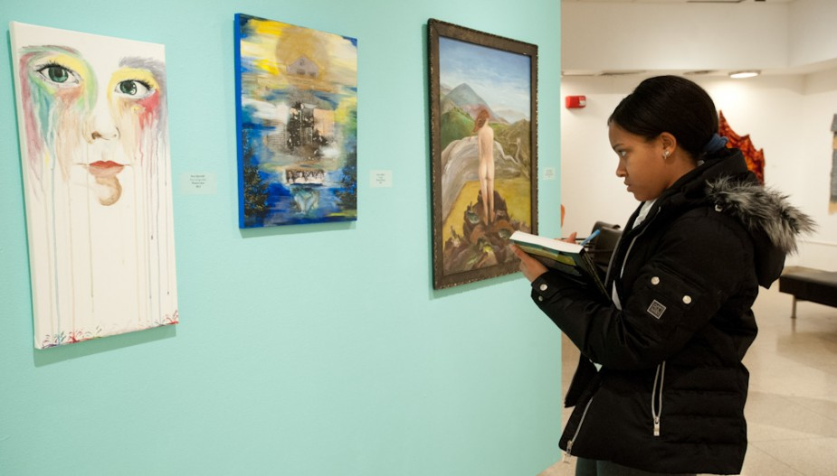Student examines artwork in gallery